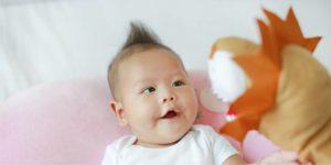 Close de bebê oriental olhando atento e sorrindo para um fantoche de leão em tom caramelo.