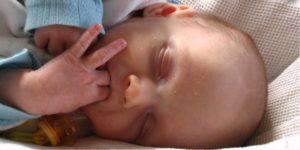 rosto de recém-nascido de olhos fechados e dedos na boca ilustra artigo sobre a visão do prematuro