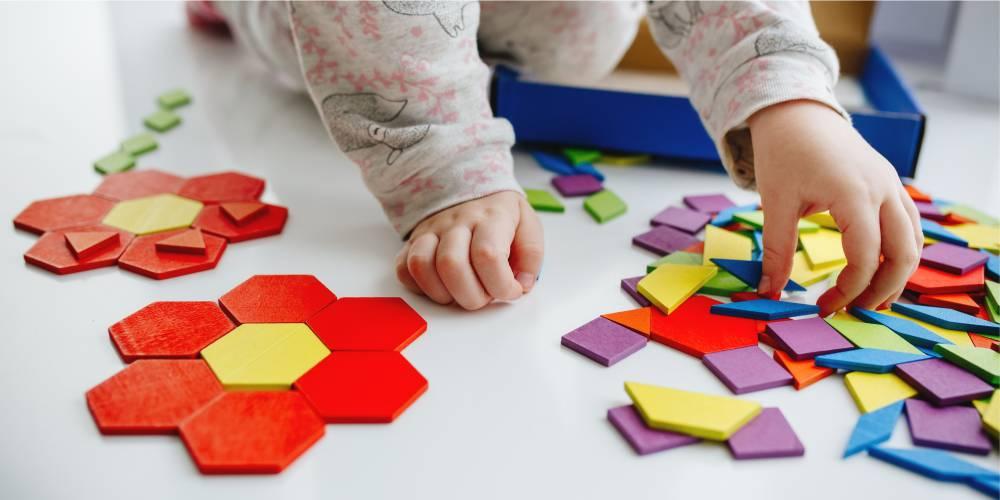 criança brinca com peças coloridas de tangram formando figuras
