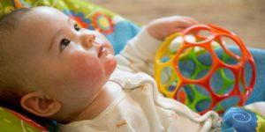 destaque para o rosto de bebê caucasiano, com bochechas rosadas, deitado sobre um tecido colorido