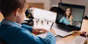 menino assiste aula online no computador
